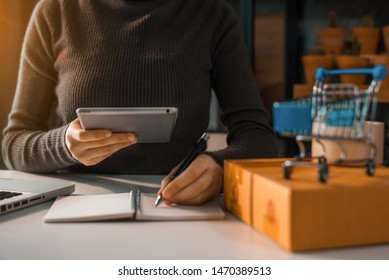 Shipping shopping online ,woman start up small business owner writing address on cardboard box at workplace.small business entrepreneur SME or freelance asian woman working with box at home.