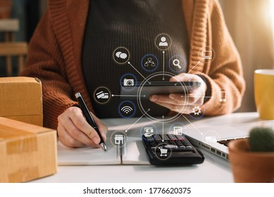Shipping shopping online ,woman start up small business owner writing address on cardboard box at workplace.small business entrepreneur SME or freelance asian woman working with box at home office.