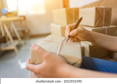 Shipping shopping online ,young start up small business owner writing address on cardboard box at workplace. seller prepare parcel boxs of product for deliver to customer.Online selling or e-commerce