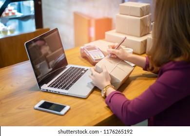 Online-Shopping, junge Firmengründer, die Adresse auf dem Karton am Arbeitsplatz schreiben.Kleine Unternehmer KMU oder freiberufliche Hobbyhure, die zu Hause mit Kisten arbeiten