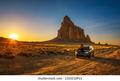 Shiprock, New Mexico, USA - May 14, 2016 : Boy enjoys sunset at Shiprock sitting on the hood of his car. Shiprock is a volcanic mountain at the high-desert plain of the Navajo Nation in New Mexico.