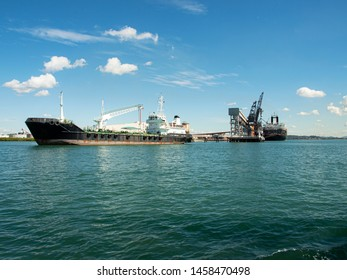 Ships berthed at the coal loader terminal Port Gladstone in tropical water with blue sky backdrop. Queensland, Australia.