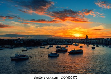 Ships and boats in the bay during beautiful sunset in city of Sliema, Malta.