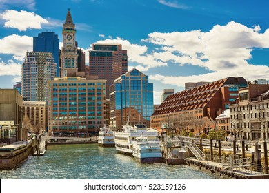 Ships and boats moored at the pier near the center of Boston in the United States. The city is surrounded by water and people often use water transport to avoid traffic jams in on the streets.