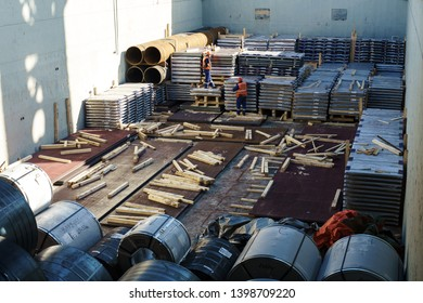 Ships in the cargo port during cargo operation. Steel in the cargo hold. Stevedors in the cargo hold
