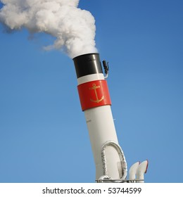 Ship's funnel with smoke from it against blue sky.