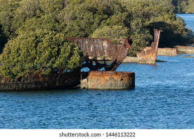 Ships Graveyard, rusted remains of a wrecked ships in a tidal mangrove forrest. Red rust corrosion and rivets. Landscape orientation background.