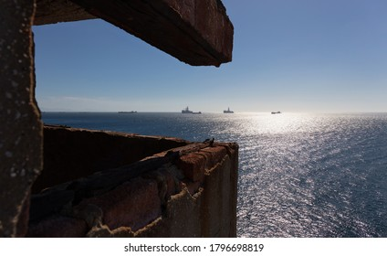 Ships near the coast of Gibraltar photographed from a historic fortress. The sun is in the sky. The back light forms reflections on the Mediterranean.