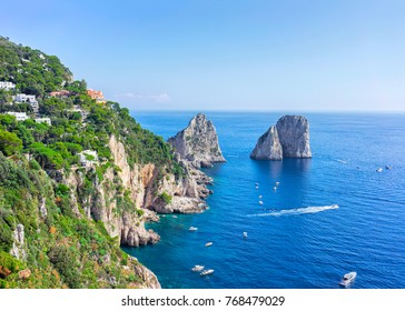 Ships near Faraglioni cliffs and Tyrrhenian Sea on Capri Island, Italy