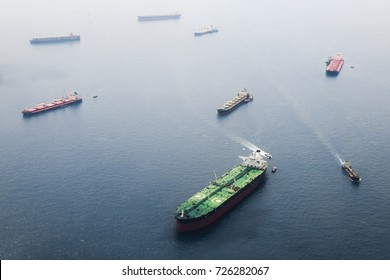 Ships in Straits of Singapore from the height. Big tanker with two helicopter platforms stay on anchor and wait for their turn to enter the port for unloading or loading
