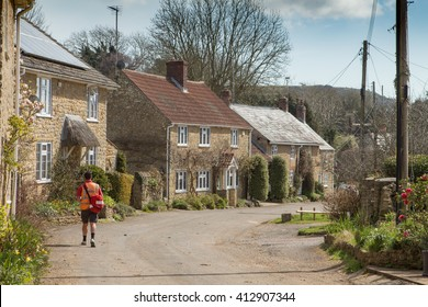 SHIPTON GORGE, UK - APRIL 12, 2016:  Postman delivers letters in pretty English village
