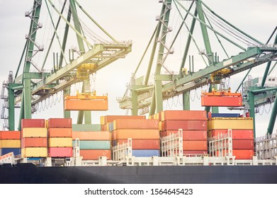 Ship-to-shore crane unloading containers from a ship in harbor enviroment. Transportation industry and shipment logistics. Export and import bussines
