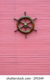 ship-wheel on the pink wooden background
