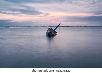 Shipwreck of fish boat at sunset in Thailand.