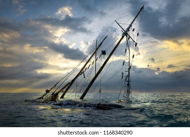Shipwreck on beach. Boat stranded on the shore. Ship submerged by the waves on sunset.