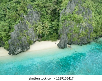 Shipwrecked solo tourist alone on a tiny wooden boat while isolated on shore of a white sand beach paradise getaway on a tropical desert island in the south Pacific ocean