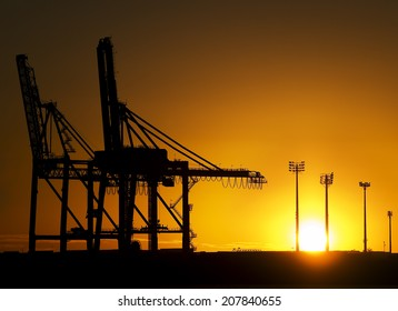 Shipyard Cranes at Sunrise. Giant container cranes photographed at Fisherman Islands Container Terminal in the Port of Brisbane, Queensland Australia.