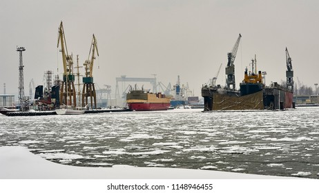 Shipyard, factory producing ships in winter, foreground on the right, dry dock