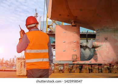 shipyard repairing and replacement of propeller of the ship in floating dock by shift engineer walkie talkie or portable radio transceiver in hand holding control worker order for maintenance.
