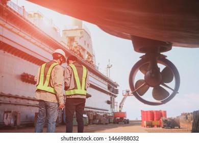 Shipyard Stern ship propeller, rudder and shafting port controller, surveyor, inspecting the final repairing of propeller on dry dock engineer planing of worker for maintenance dry dock in shipyard.
