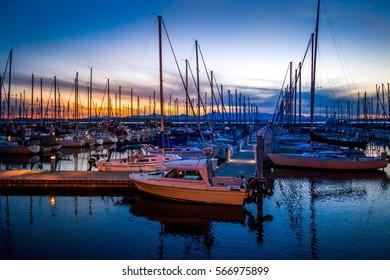 A shipyard at sunset lined with boats on still water with mountains and feathery clouds in the background  in Seattle, Washington at Golden Gardens Park.
