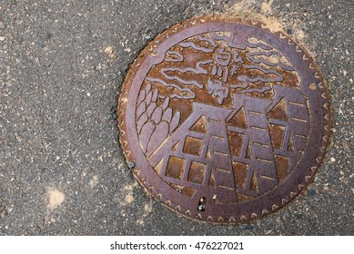 Shirakawa-go, Japan - May 3, 2016: Manhole cover of Shirakawago village, Gifu Prefecture, Japan. The Gassho Style houses engraved on to a manhole cover as a symbol of an important village's landmark.