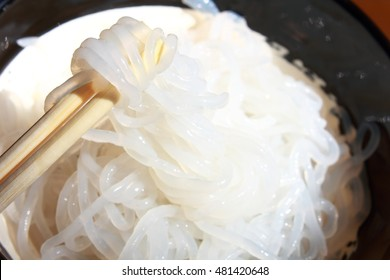 Shirataki noodles in black plate lifted by wooden chopsticks