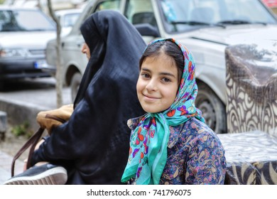 Shiraz, Iran - 19 april, 2017: Mature woman and a girl about 8 years old sat down to rest on a city street.