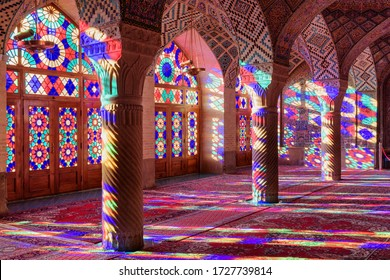 Shiraz, Iran - 31 October, 2018: Scenic morning view of prayer hall at the Nasir al-Mulk Mosque (Pink Mosque). Sunlight reflected through stained glass windows on columns, the wall and the floor.