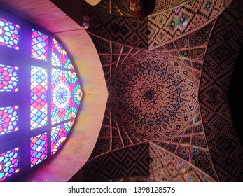 Shiraz, Iran - April 16 2019. Arched window with colorful stained glass and elaborate Islamic tiles pattern on the ceiling of Nasir al-Mulk Mosque or Pink Mosque in Shiraz, Iran.
