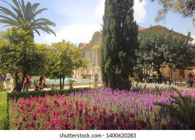 Shiraz, Iran - April 17 2019. Colorful flowers with a cypress tree near the Qavam House in Eram Garden of Shiraz, Iran.