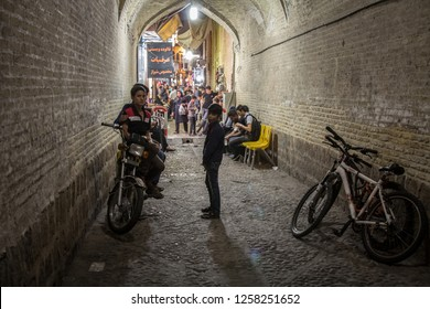 SHIRAZ, IRAN - AUGUST 15, 2016: Children and teenagers, boys, standing on bicycles and motorcycles in an alley of Vakil Bazar, the main covered market of the Iranian city