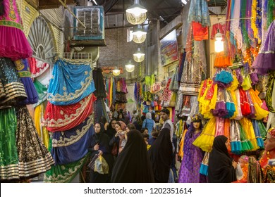 SHIRAZ, IRAN - AUGUST 16, 2018: Street of the Shiraz Vakil bazar with women checking traditional colorful clothes and muslim veils. Symbol of Persian architecture, it's a major landmark of the city