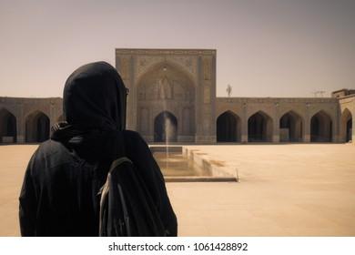 Shiraz, Iran - March 06, 2018: One woman tourists wearing black chador in courtyard Vakil Mosque of Shiraz.