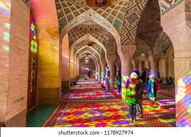 Shiraz, Iran - March 06, 2018: Lot of tourists taking photos in the interior of Nasir Al-Mulk Mosque (Pink Mosque) with colorful shining stained glass windows.