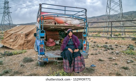 Shiraz, Iran - May 2019: Qashqai nomadic woman sitting at the back of her old car. The Qasqhai are nomadic people living in temporary villages.