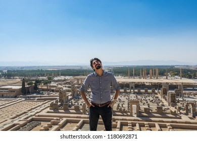 Shiraz, Iran, November 10th, 2017: An Iranian man standing with aerial view of Persepolis in Shiraz, Iran. The ceremonial capital of the Achaemenid Empire. UNESCO World Heritage