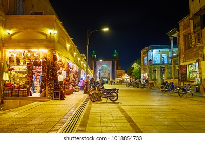 SHIRAZ, IRAN - OCTOBER 12, 2017: The walk along the stores of Vakil Bazaar to the medieval iwan (portal) of Vakil mosque, decorated with evening lights, on October 12 in Shiraz.