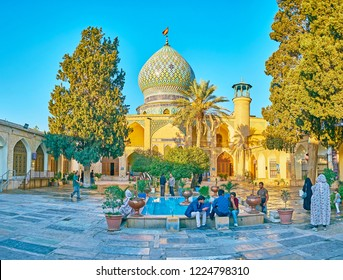 SHIRAZ, IRAN - OCTOBER 12, 2017: The courtyard of Imamzadeh Ali Ibn Hamzeh Holy Shrine with small garden, fountain and beautiful Persian architecture, on October 12 in Shiraz