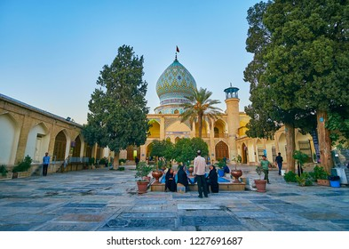 SHIRAZ, IRAN - OCTOBER 12, 2017: The visitors of Imamzadeh Ali Ibn Hamzeh Holy Shrine relax at its scenic garden, located in courtyard, on October 12 in Shiraz