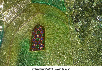 SHIRAZ, IRAN - OCTOBER 12, 2017: The intericate mirror pattern around stained-glass window in arch of Mirror Hall of Imamzadeh Ali Ibn Hamzeh Shrine, on October 12 in Shiraz