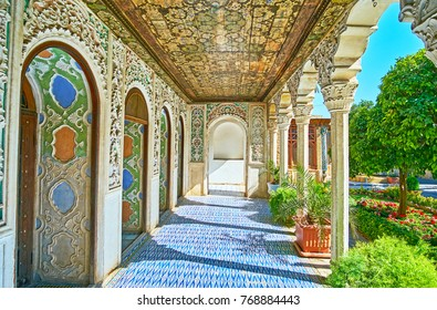 SHIRAZ, IRAN - OCTOBER 12, 2017: The richly decorated covered gallery of Zinat Ol-Molk mansion is neighboring with its lush shady garden, on October 12 in Shiraz.