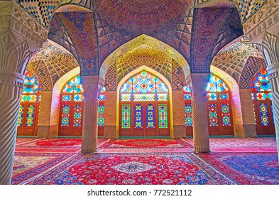 SHIRAZ, IRAN - OCTOBER 12, 2017: Interior of winter prayer hall of Nasir Ol-Molk mosque with beautiful stained glass windows, stone carved columns and fine tiled patterns, on October 12 in Shiraz.