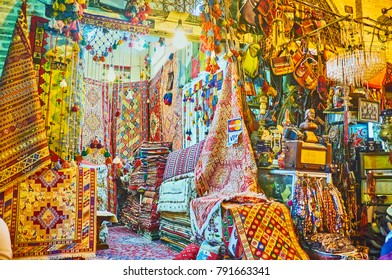 SHIRAZ, IRAN - OCTOBER 12, 2017: Carpet stall with colored kilims and rugs, covered with patterns, neighbors with antique stall with souvenirs and jewelries, Vakil Bazaar, on October 12 in Shiraz.