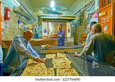 SHIRAZ, IRAN - OCTOBER 13, 2017: The old bakery works in the evening, clients come after work and wait for the fresh flatbread, on October 13 in Shiraz.