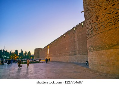 SHIRAZ, IRAN - OCTOBER 14, 2017: The frontage wall of Karim Khan citadel stretches along the crowded Shohada Square, decorated with flower beds and ornamental garden, on October 14 in Shiraz.