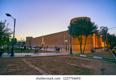 SHIRAZ, IRAN - OCTOBER 14, 2017: People walk around Shohada Square with a view on old Karim Khan citadel on twilight, on October 14 in Shiraz.
