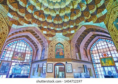 SHIRAZ, IRAN - OCTOBER 14, 2017: Interior of  Kolah Farangi decorated with ornate dome with muqarnas and fine floral patterns and arched stained glass windows, on October 14 in Shiraz