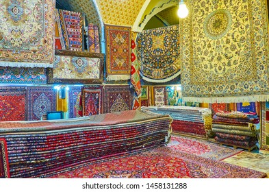 SHIRAZ, IRAN - OCTOBER 14, 2017: Interior of carpet market in old Shiraz Bazaar with heap of large carpets and different hanging rugs, on October 14 in Shiraz.