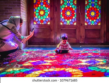 Shiraz, Iran - October 23, 2016: Iranian woman takes photo of baby in Nasir ol Molk Mosque also known as Pink Mosque in Shiraz, one of the most famous mosques in Iran